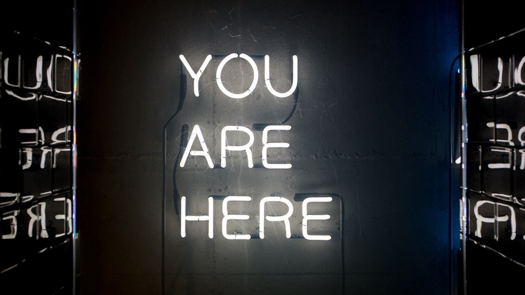 "White neon sign reading ""You Are Here"" hanging on a black wall"