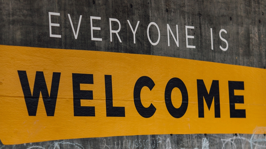 "The phrase ""Everyone is Welcome"" painted on a concrete wall"