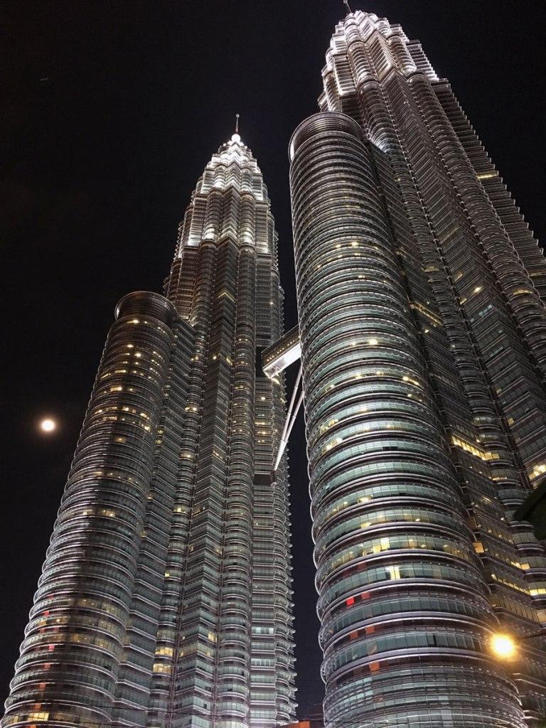 lit up metal skyscrapers against a black night sky shot from below looking upwards