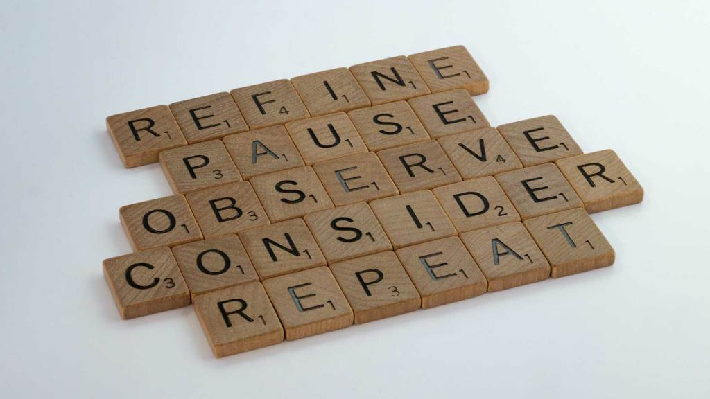 Wooden Scrabble tiles spelling out Refine Pause Observe Consider Repeat against a white backdrop.