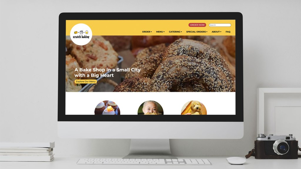 Desktop computer screen  on a white desk with a webpage for Scratch Baking featuring a photo with bagels
