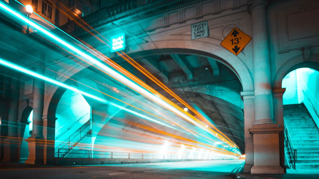 Traffic seen as streaks of colorful light going through a tunnel at night.