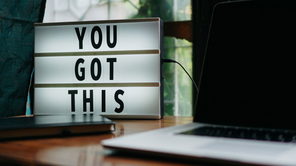 "Light up sign saying ""You Got This"" sitting on a wooden desk next to an open laptop."