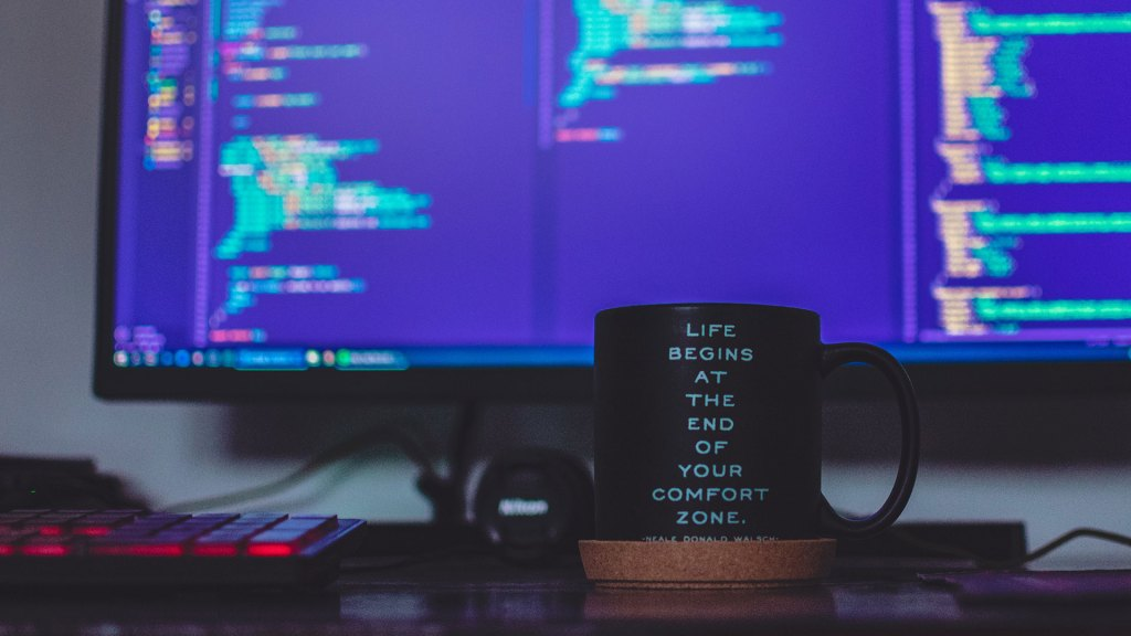 "Black coffee mug with ""Life begins at the end of your comfort zone"" written on it sitting in front of computer screen with code on it."