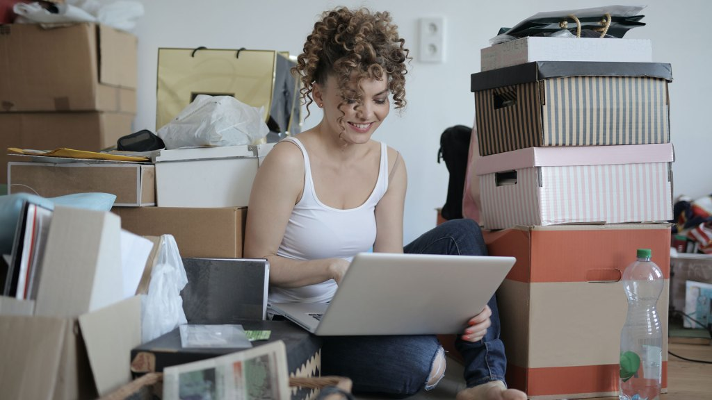 Woman sitting on floor looking at laptop screen surroundeded by boxes and a mess of book, paper, and bags