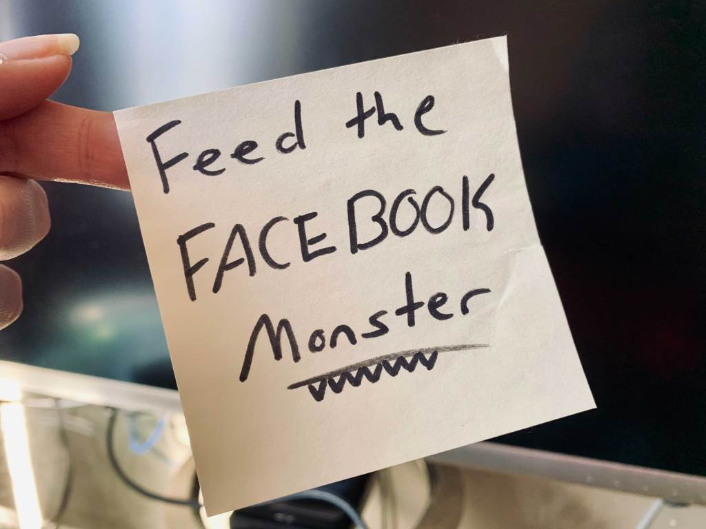 """Post-it note being held by hand that says """"Feed the Facebook Monster"""""""