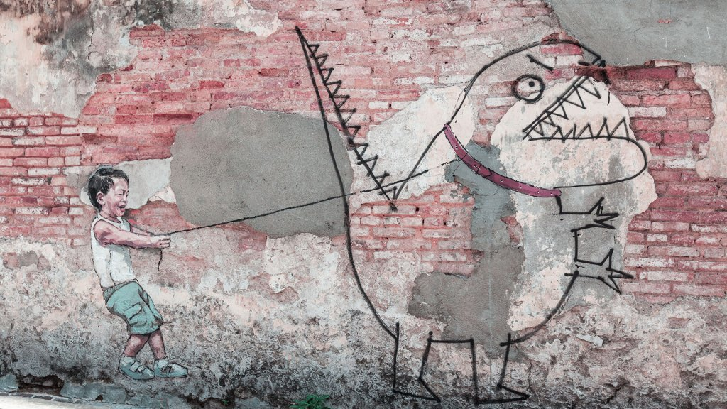Graffiti on a brick wall depicting a little boy holding the leash of a monster which looks like it was hand drawn by a child.